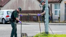 A police officer carries out a search near the murder scene