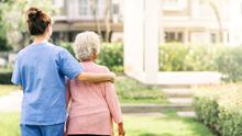 Vulnerable: A caregiver walking with elderly woman