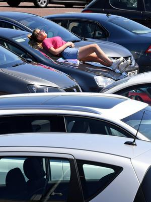 A girl sunbathing on her car in a Co Antrim shopping centre