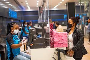 A staff member and customer wear masks, with a protective screen at the till, inside Primark in Oxford Street this week