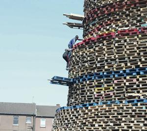 Young loyalists scale the huge face of the bonfire on Lanark Way, off the Shankill