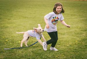 Khara Pringle's daughter Ayria and their golden retriever pup Khalissi in the NHS T-shirts