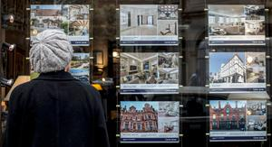 Demand: A woman looking at houses for sale inan estate agents window