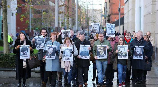 Family members outside Laganside Courts in Belfast hold images of some of those who were killed in disputed circumstances over the course of three days between August 9 and August 11 1971 (Niall Carson/PA)