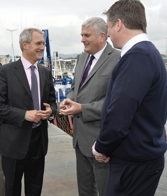 Owen Paterson with Alan McCulla, of Anglo-North Irish Fish Producers Organisation, and Jim Wells speak to fishermen in Kilkeel earlier yesterday