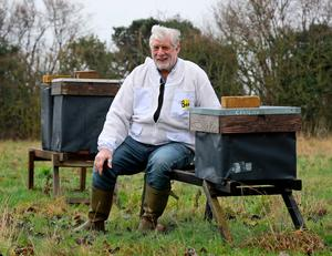 Beekeeper Patrick Murfet with some of his hives in an orchard near Canterbury in Kent