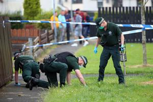 Police search at the scene of an overnight shooting in which a house was attacked in Ballymena