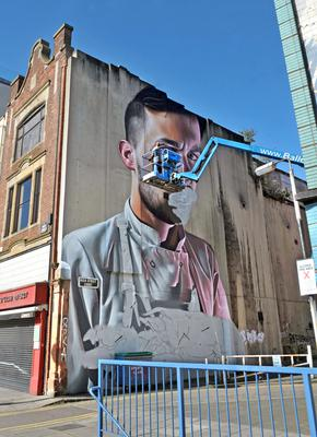 A graffiti artist works on a new painting in Belfast