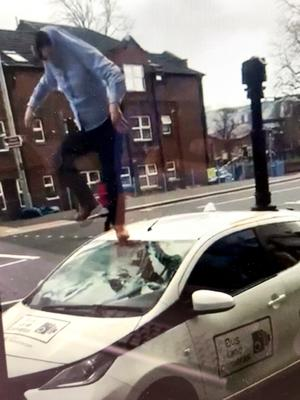 A man stamping on the roof of a bus lane camera vehicle in April