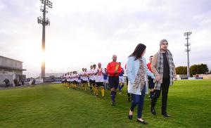 Mark and Terri-Louise lead out the teams at a match fundraiser during his illness