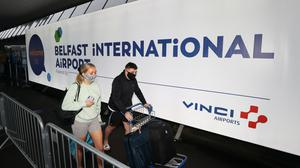 Travellers arriving at Belfast International Airport (PA)