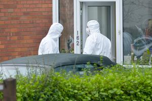 Forensic officers collect evidence outside the Greenisland house