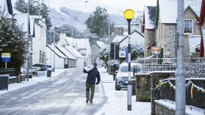 A man walks through the snow in Killin, Stirlingshire (PA)