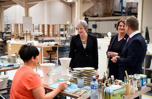 Mrs May speaks to workers at the factory