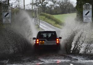 Motorists struggle through floods in Glenavy, Co Antrim, amid warnings of heavy rain and strong winds as Storm Desmond arrives in Northern Ireland this weekend