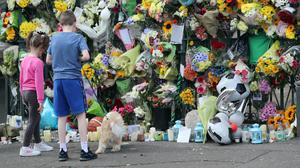 Children lay a floral tribute to Noah Donahoe at the gates of his school, St Malachy's College in Belfast
