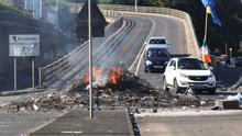 Motorists attempt to drive past the remains of the huge bonfire in the Bogside in Derry last August