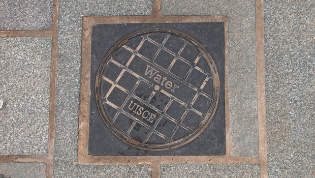 A manhole cover in Ballymena including the Irish word for water
