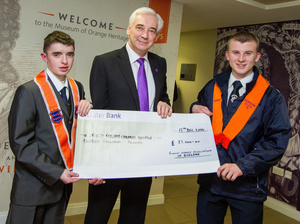 Northern Ireland Children's Hospice president Paul Clark is presented with a cheque by junior Orangemen David Perry and Christopher Hutchinson