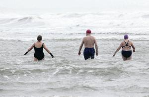 Hardy swimmers plunge into the surf at Newcastle