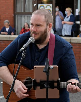 Singer David Jackson, a former contestant on The Voice UK, entertains staff and residents with an impromptu concert outside Clifton Nursing Home in north Belfast yesterday