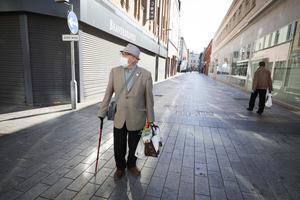 A member of the public wearing a face mask walks through a deserted Belfast city centre