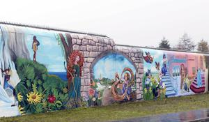 The mural featuring cartoon images which has transformed the peace line in west Belfast near the Sliabh Dubh estate off the Springfield Road