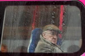 A man stares out through the bus window at the weather 2014