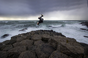 Nye Frankie Newman performing a somersault at the Giant's Causeway
