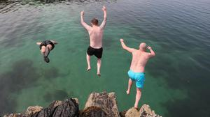 Taking the plunge: Tristan Brennan, Gary Niblock and Jamie Craig take a dive off the rocks at Orlock, Co Down