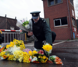 A police officer lays floral tributes at the gates of Massereene Barracks after the attack in 2009