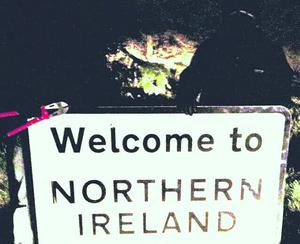 Two men with bolt cutters pictured posing with the Welcome To Northern Ireland sign. The sign was cut down and stolen just days after it was erected at the border town of Strabane, County Tyrone.