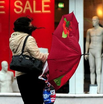 A woman struggles with an umbrella in the wind and rain while doing some last-minute shopping in Derby city centre