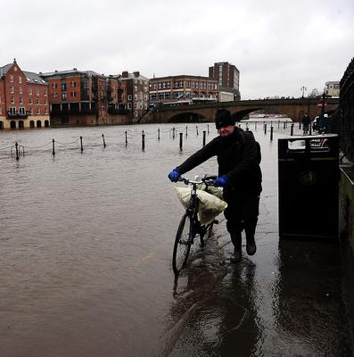 Rising water levels from the River Ouse bring floodwater into riverside roads in York City centre as heavy rain and gales sweep across many parts of the UK
