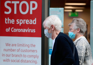 Safety measures: Members of the public wearing face masks walk past a sign in a bank window