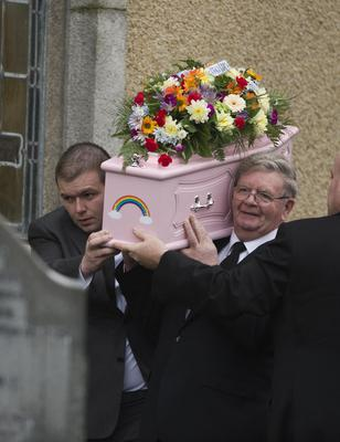 Lucy's father David (above left) helps carry her coffin
