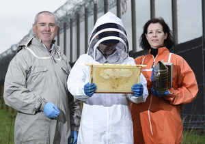 Chris Hodges, from the Ulster Beekeeping Association, and Rachel Armstrong, security manager at Hydebank, with one of the students