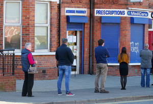 People stand 2m apart as they queue for prescriptions