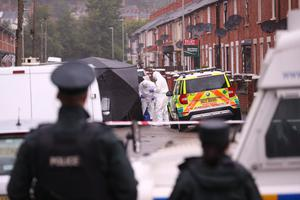 Police and forensic officers at the scene of Saturday's gun attack in west Belfast