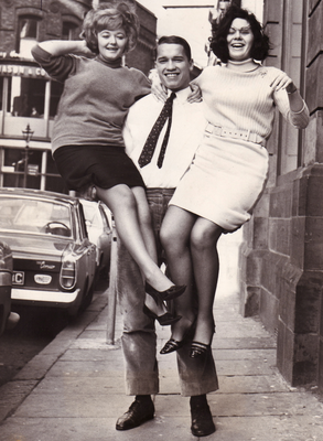 Arnold Schwarzenegger with Sandra Burrows from Belfast and Deirdre Cullen from Dunmurry after winning a bodybuilding competition at the Park Avenue Hotel