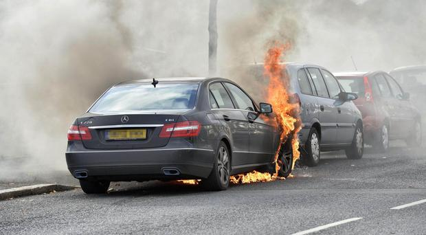 Fire crews extinguish a Mercedes car on fire on the Ballysillan Road in Belfast