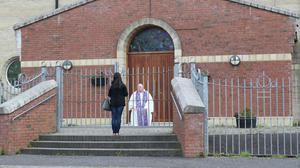 Fr Paddy McCafferty hears confessions while observing social distancing though the locked gates of Corpus Christi Church in Ballymurphy, West Belfast (Niall Carson/PA)