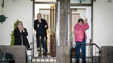 Other residents in the New Lodge area of Belfast join in the clapping
