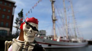 A toy skeleton pirate is seen in front of the Polish Navy training ship the ORP Iskra, one of 50 vessels arriving in Belfast for the Tall Ships Festival