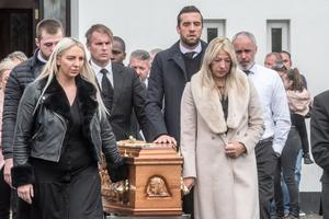Republic of Ireland footballer Shane Duffy places his hand on his dad Brian's coffin while his mum Siobhan (front right) leads mourners from the church in Galliagh
