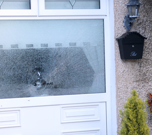 A bullet hole in the front window of a house in Cranbrook Court that was attacked on Monday night