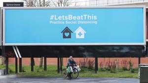 A man pushes a bicycle laden with bags as he passes by a sign in Belfast urging the public to practise social distancing (PA)