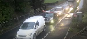Cars duck under the level crossing barrier in Cullybackey