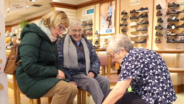 Staff member Edna Alexander helps customers Nan Scullion and Jane Thompson shop for a new pair of shoes