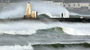 A man and dog brave the elements as they walk along the wall at the Barmouth on Castlerock beach